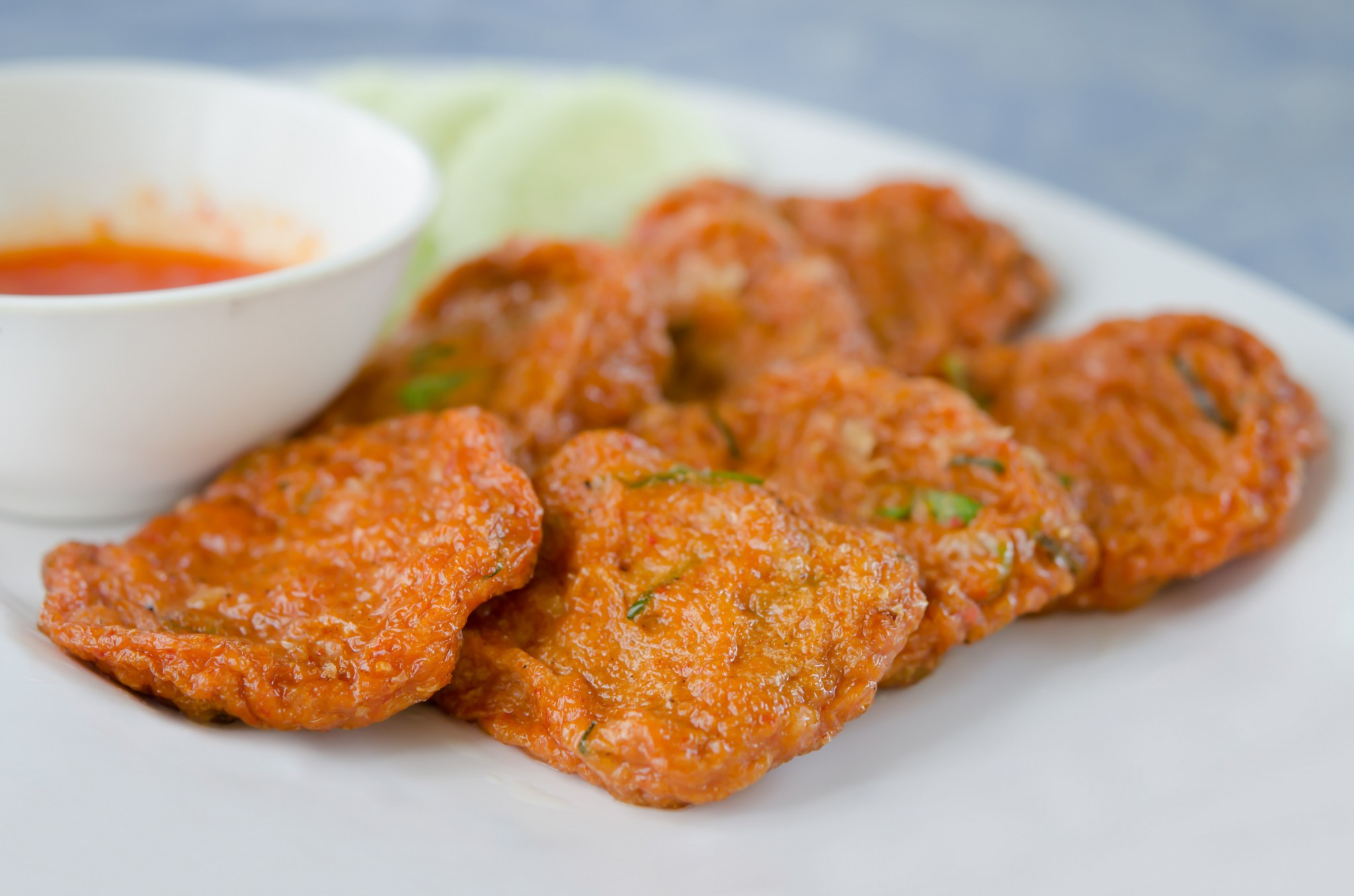 Spicy fried fish cake (Tod Mun Pla) served with cucumber  and  sweet sauce
